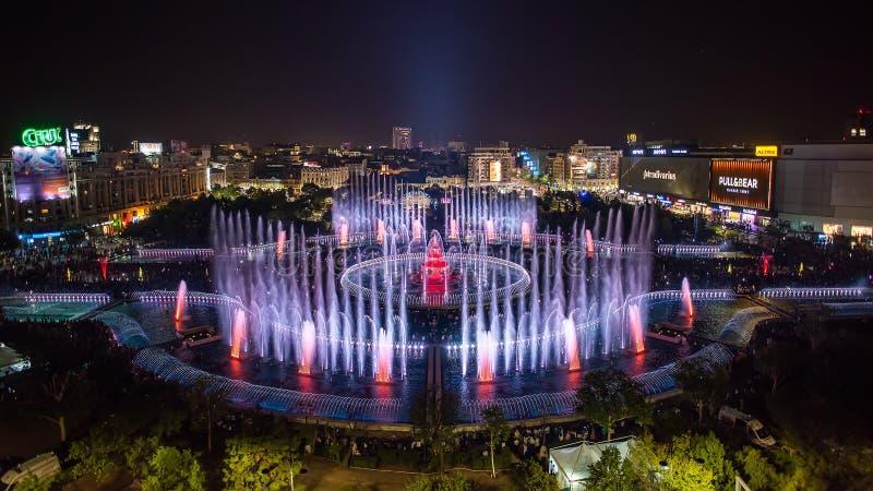 布加勒斯特市中央Unirii方形的新的2018年喷泉全景和夜城市地平线 免版税图库摄影