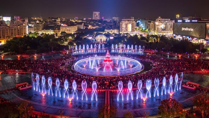 布加勒斯特市中央Unirii方形的新的2018年喷泉全景和夜城市地平线 免版税库存照片