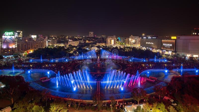 布加勒斯特市中央Unirii方形的新的2018年喷泉全景和夜城市地平线 库存照片