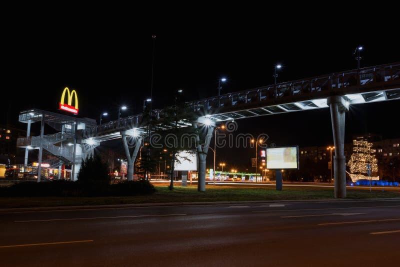 布尔加斯,保加利亚- 2018年2月1日:顶上的步行桥在晚上 麦克唐纳` s餐馆商标 库存图片