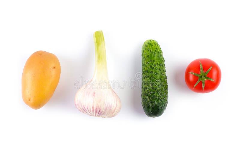 布局由土豆、大蒜、蕃茄和黄瓜制成在白色背景 平的位置 在倾吐的餐馆沙拉的主厨概念食物新鲜的厨房油橄榄 免版税图库摄影