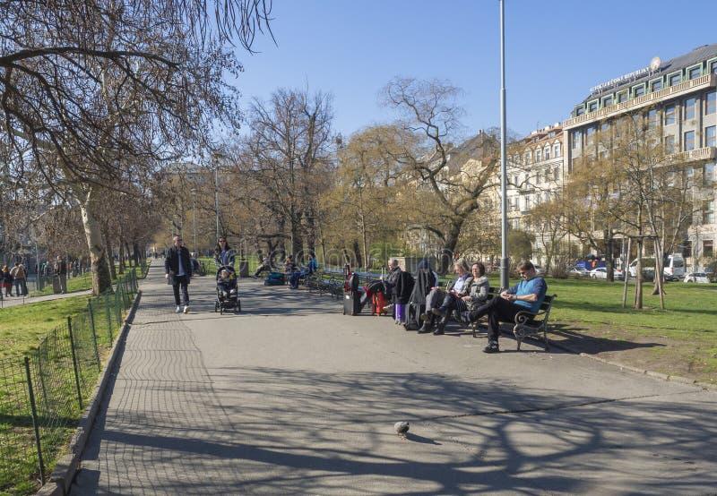 布拉格,捷克,2019年3月23日:人们走和坐长凳在布拉格主要火车前面的公园路 免版税图库摄影
