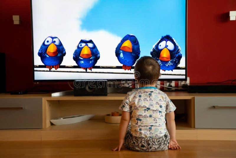 布拉格,捷克-18 03 2019年:有唐氏综合症观看的动画片的小男孩 库存图片