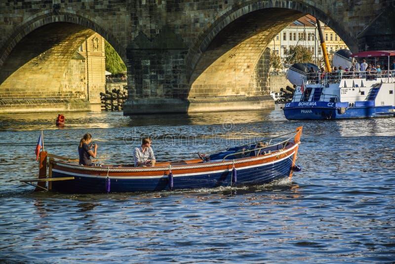 布拉格,捷克- 2019年9月,17日:夫妇在查尔斯附近享受在一条小船的浪漫日落在伏尔塔瓦河河 免版税库存图片