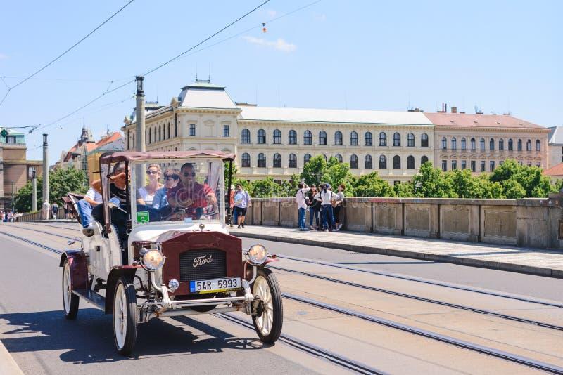 布拉格,捷克- 2017年5月:Czechia人旅客人用途服务白色经典减速火箭的汽车在的城市附近游览 免版税库存照片