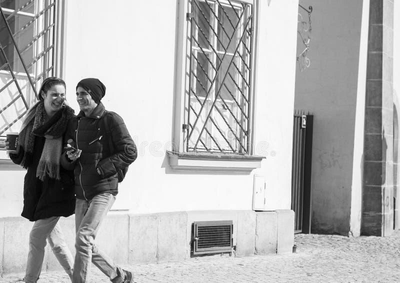 布拉格,捷克- 2017年3月14日:年轻夫妇饮用的咖啡,当步行沿着向下街道时 桥梁黑白图象 库存图片