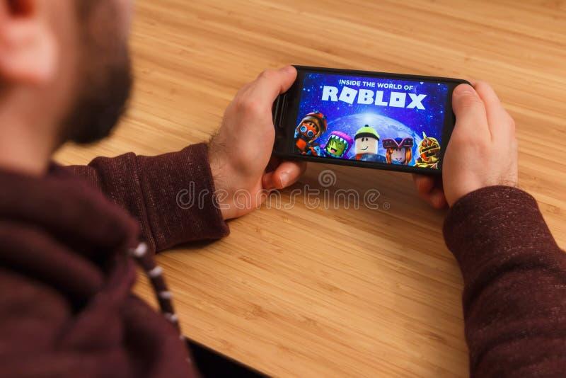 布拉格,捷克- 2019年3月16日:拿着智能手机和playng的人Roblox流动比赛 一个说明社论 免版税库存图片