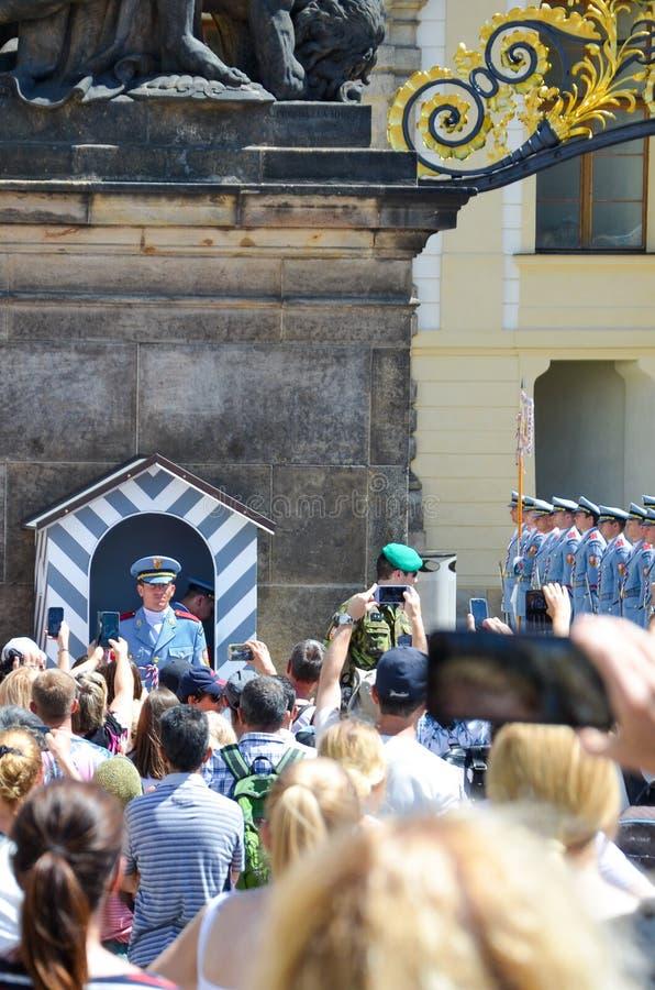 布拉格,捷克- 2019年6月27日:观看和为在布拉格城堡前面的人群城堡卫兵照相 卫兵和 库存图片