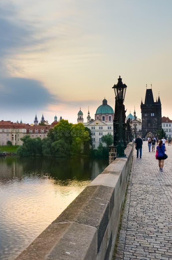 布拉格,捷克- 2019年6月27日:走在历史查理大桥的人们在清早 日出光 ?? 图库摄影