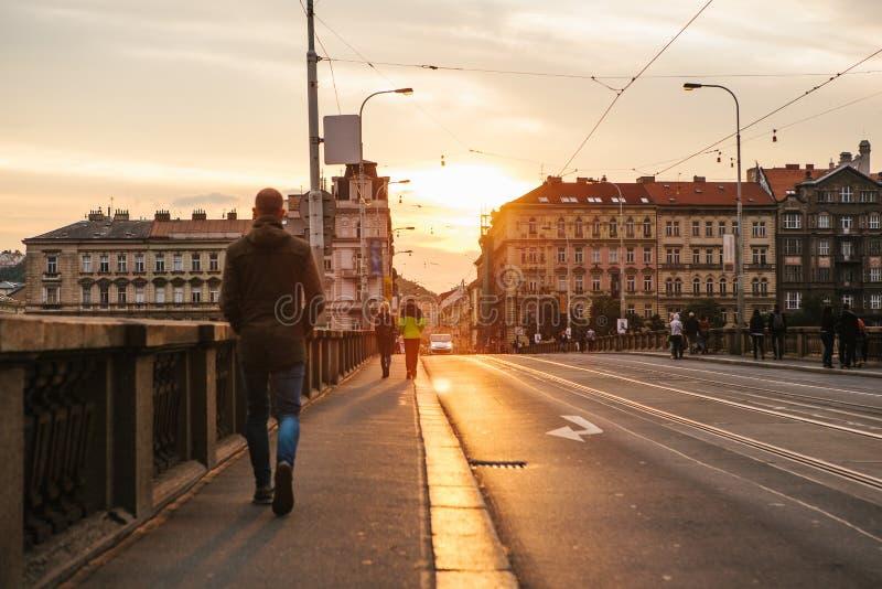 布拉格, 2017年9月23日:人们在桥梁走或走在日落 传统捷克建筑学 图库摄影