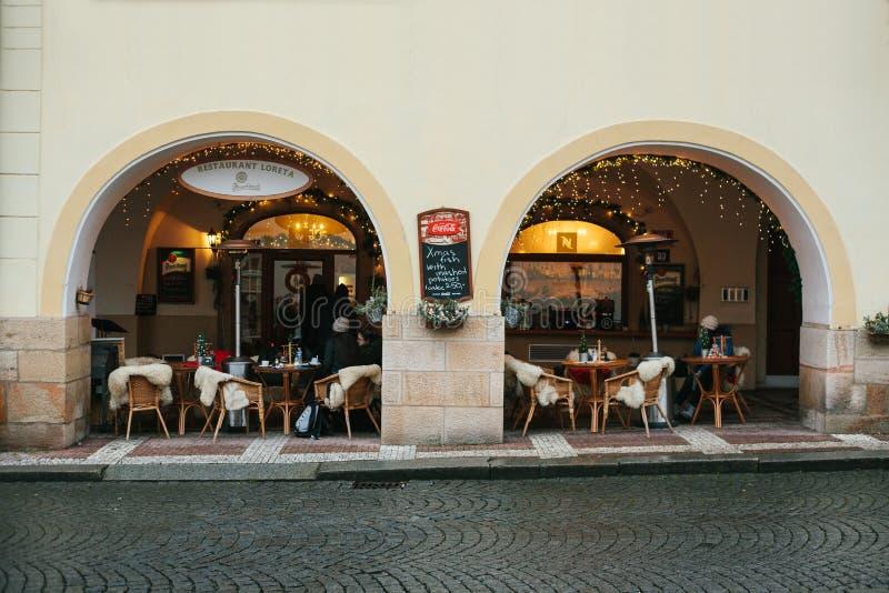 布拉格, 2016年12月25日:在街道上的舒适咖啡馆-有桌、藤椅和绵羊地毯的与圣诞节装饰 库存图片