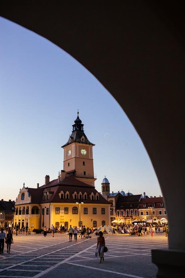 布拉索夫,罗马尼亚- 2017年8月1日:中央理事会正方形的(皮亚塔Sfatului)人们与城镇厅钟楼在夏天晚上 免版税库存图片