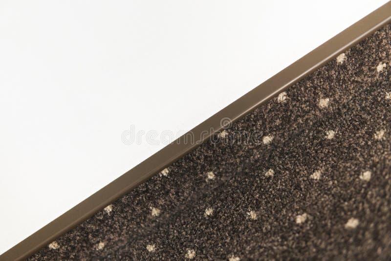 布朗与的地毯地板与一个地毯护壁板的白色小点在白色墙壁上 免版税库存图片