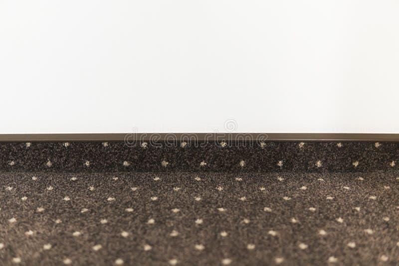 布朗与的地毯地板与一个地毯护壁板的白色小点在白色墙壁上 库存图片