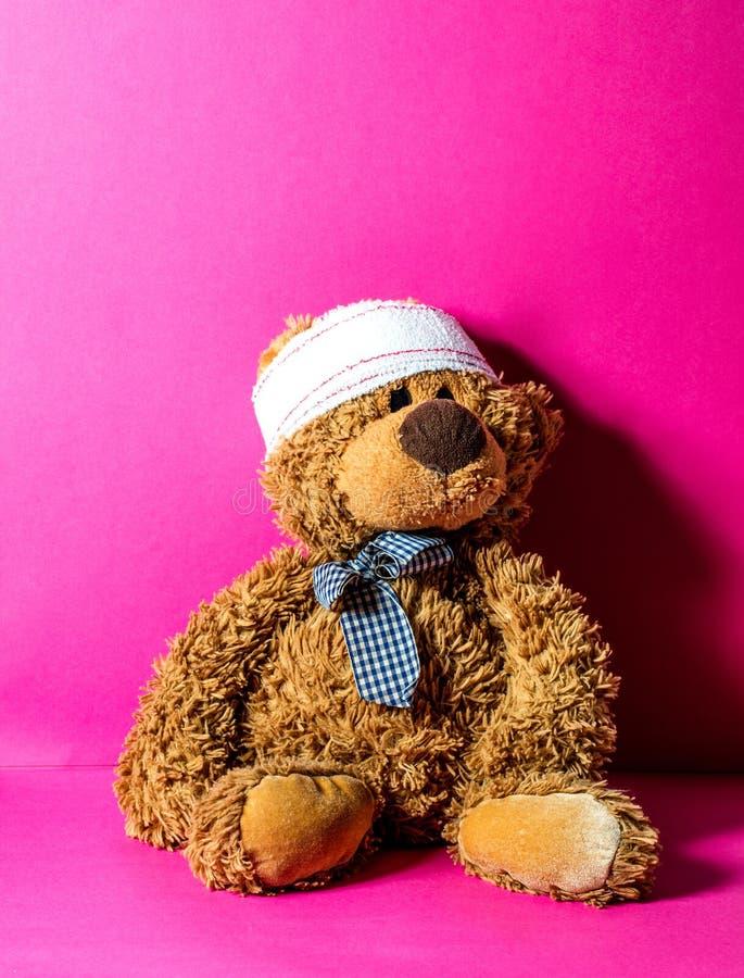布朗与绷带的玩具熊在儿科医生的头 免版税库存照片