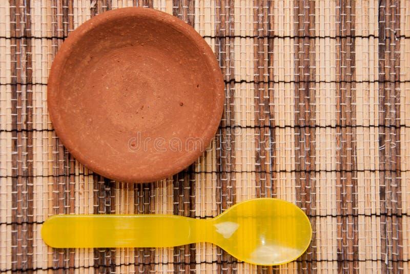 布朗与黄色塑料匙子的黏土盘 免版税库存照片