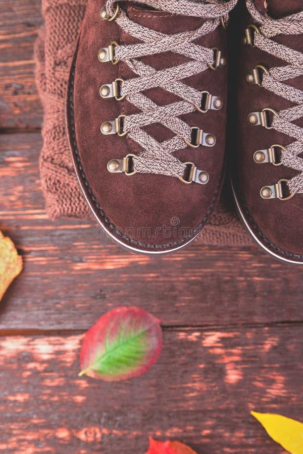 布朗人与毛线衣的绒面革起动在木背景 免版税库存图片