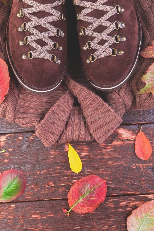 布朗人与毛线衣的绒面革起动在木背景 库存照片