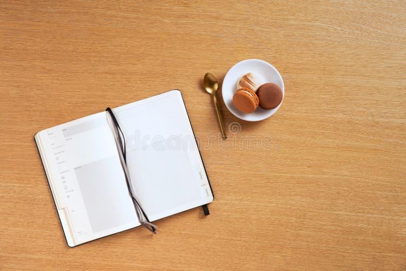 布朗和白色法国蛋白杏仁饼干在一块板材有一把金黄茶匙子的由一个空白的食谱笔记本在橡木背景 库存图片