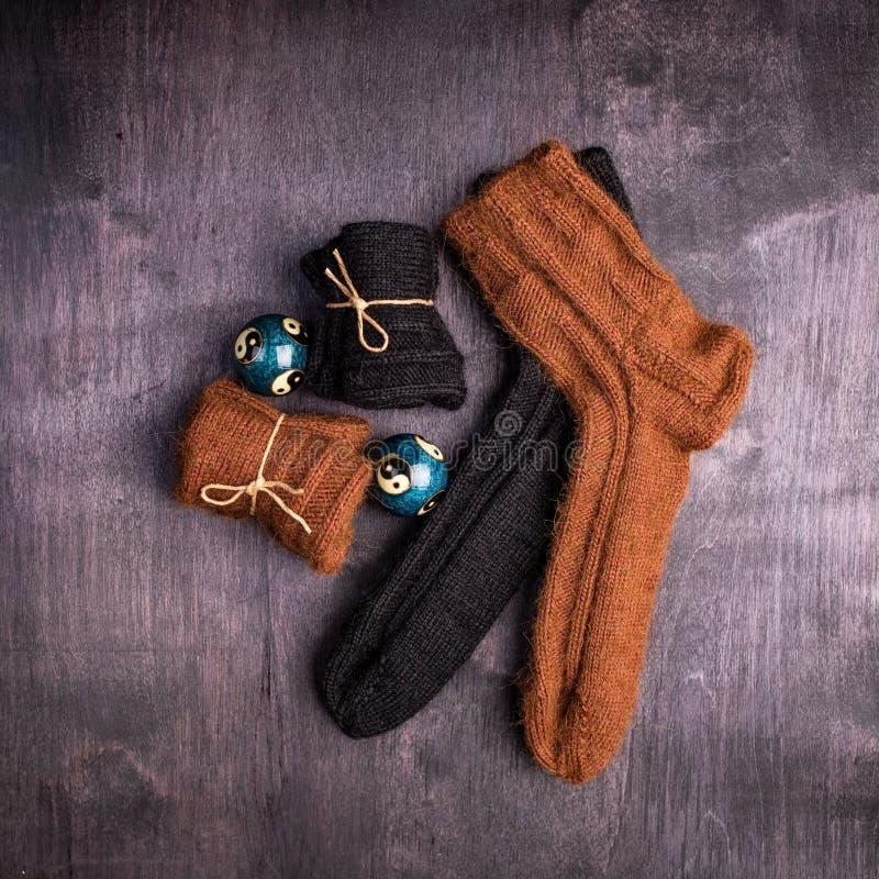 布朗和黑被编织的袜子和球在黑色和灰色背景 免版税库存照片