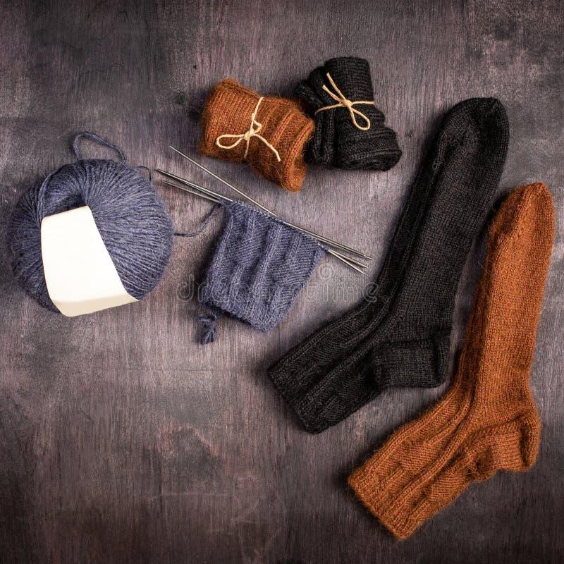 布朗和黑被编织的袜子,灰色球毛线和编织在黑色和灰色木背景 库存照片