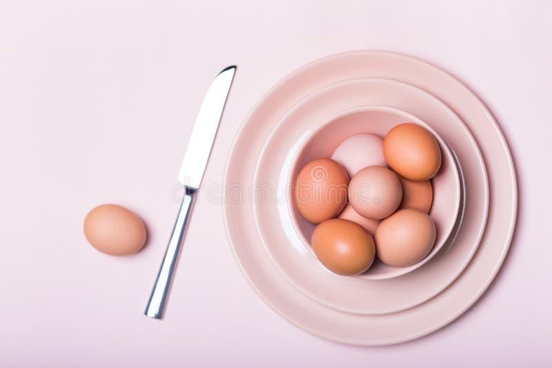 布朗在一块板材的鸡鸡蛋有在一张木桌上的一把刀子的 库存照片