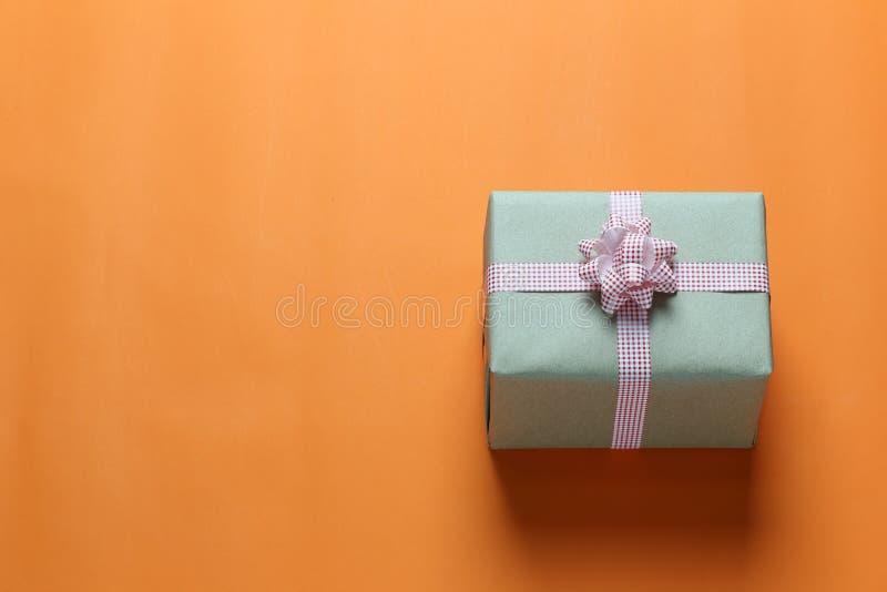 布朗在橙色加工印刷纸地板安置的圣诞礼物箱子和 免版税库存图片