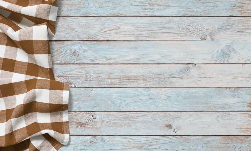布朗在蓝色木桌上的野餐布料 免版税库存图片