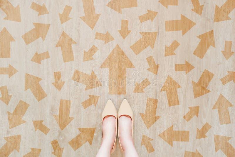 布朗在路街道上的箭头选择,去前面概念 女性身分和许多不同的方向箭头标示用裸体鞋子 库存照片
