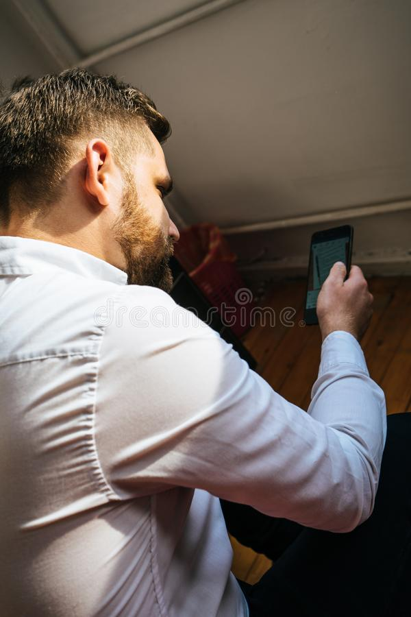 布朗头发土耳其人典雅在坐在他的床上的白色衬衫检查他的智能手机读书消息 库存图片