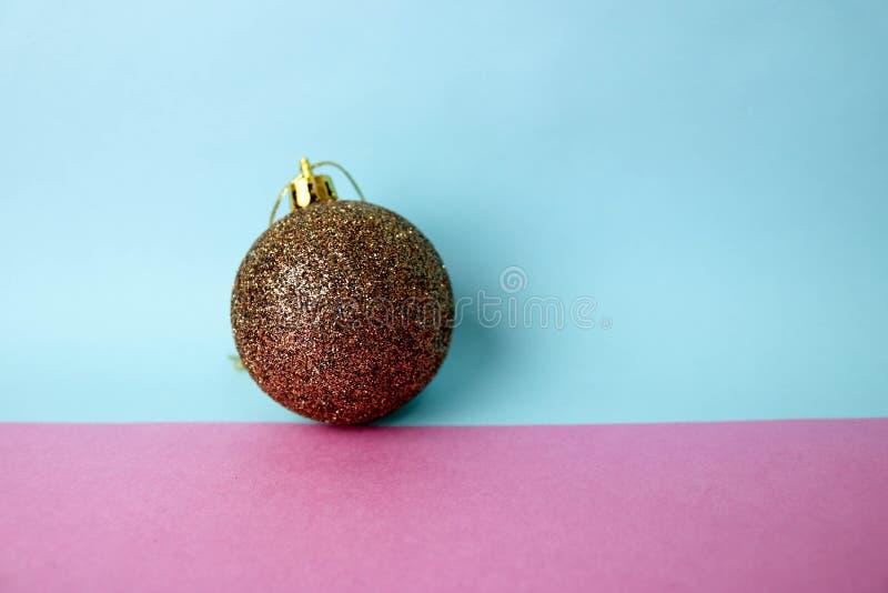 布朗小回合玻璃xmas欢乐圣诞节球,圣诞节玩具涂灰泥在与在桃红色紫色蓝色背景的衣服饰物之小金属片 库存图片