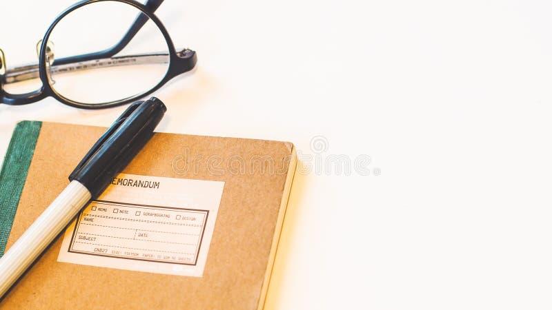 布朗工艺纸盖子笔记本有笔和镜片白色背景 库存照片