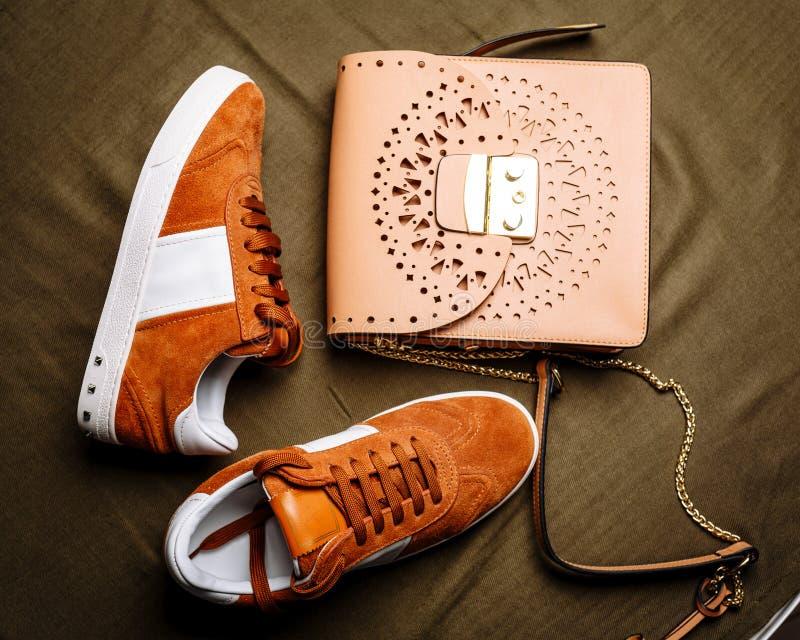 布朗有白色口音的绒面革运动鞋在白色脚底和一个棕色皮包与一把金黄锁在绿色被编织的背景 图库摄影