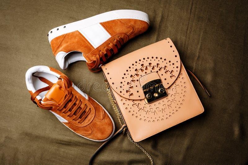 布朗有白色口音的绒面革运动鞋在白色脚底和一个棕色皮包与一把金黄锁在绿色被编织的背景 库存照片