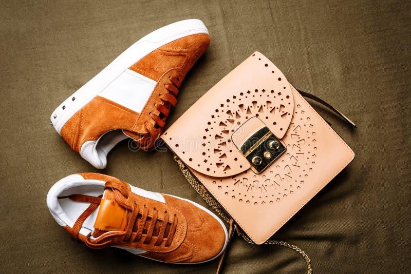 布朗有白色口音的绒面革运动鞋在白色脚底和一个棕色皮包与一把金黄锁在绿色被编织的背景 免版税库存照片