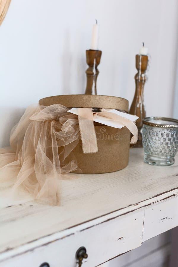 布朗有礼服的工艺箱子在白色木桌上 免版税库存照片