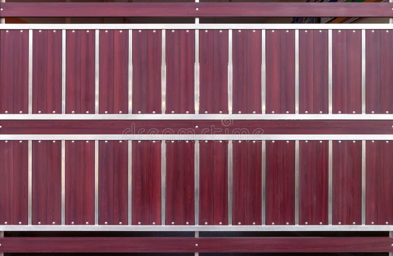 布朗木和不锈的篱芭背景、板条或者墙壁纹理 免版税库存图片