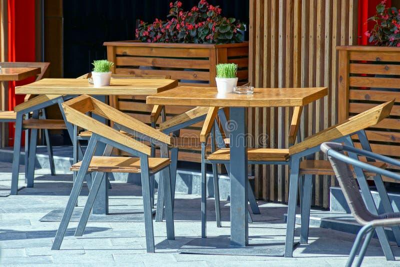 布朗木桌和椅子在边路外面在夏天咖啡馆 免版税库存图片