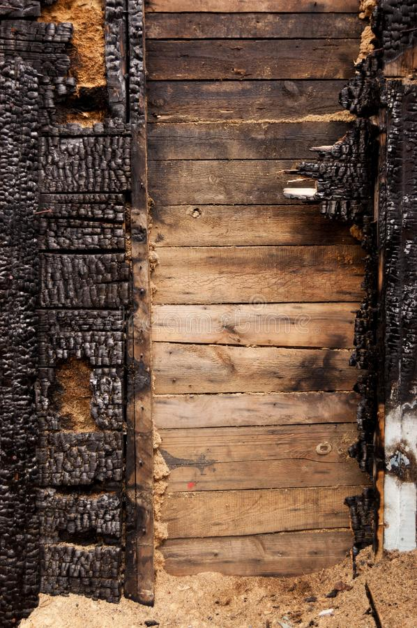 布朗烧了木板条房子墙壁与压印的纹理的 拷贝空间的背景 不动产损失的概念或 免版税库存照片