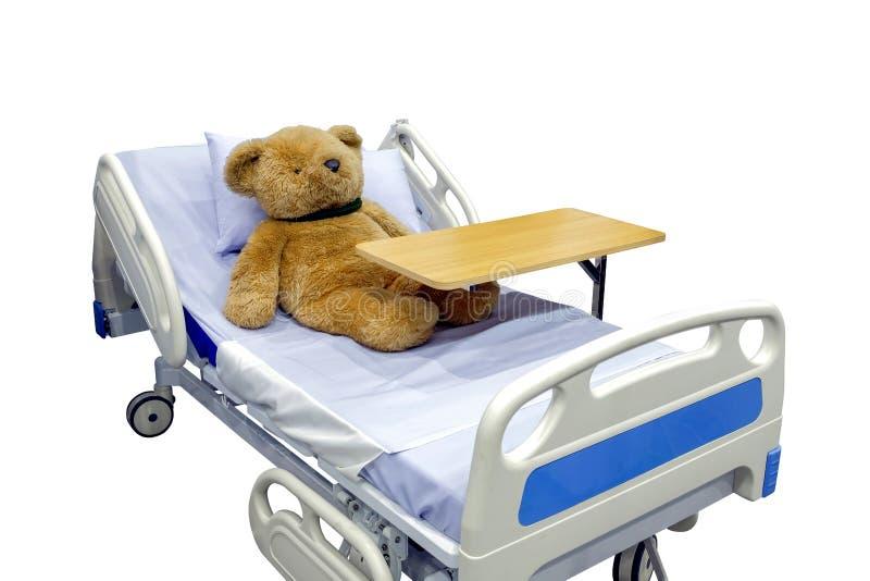 布朗玩具熊说谎的病残在与overbed桌的床上在身体 图库摄影
