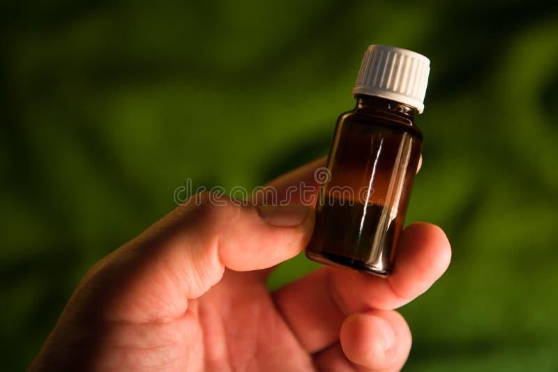 布朗玻璃医学瓶用手 库存图片