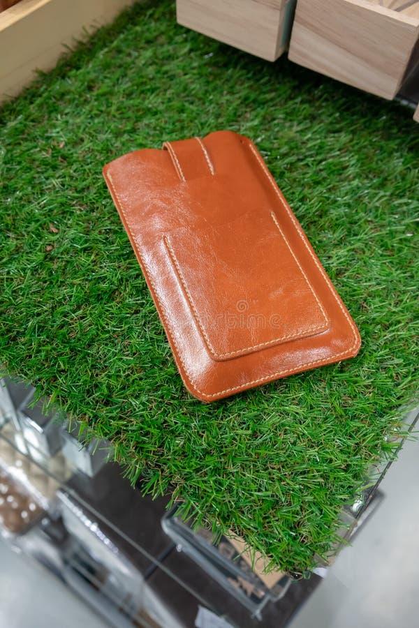 布朗用皮革包盖在人为草的电话盒显示的 免版税库存图片