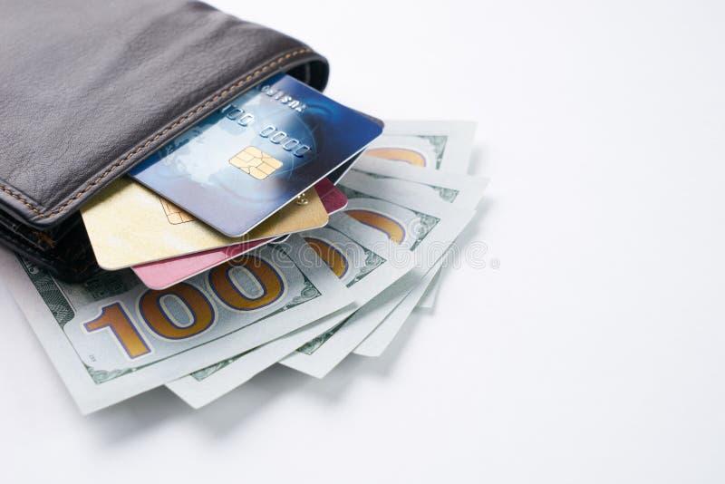 布朗用皮革包盖有信用、借方、折扣卡片和美元的钱包 图库摄影