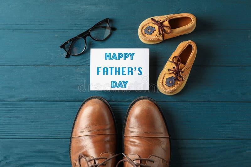 布朗皮鞋、儿童的鞋子、题字愉快的父亲节和玻璃在木背景 库存图片