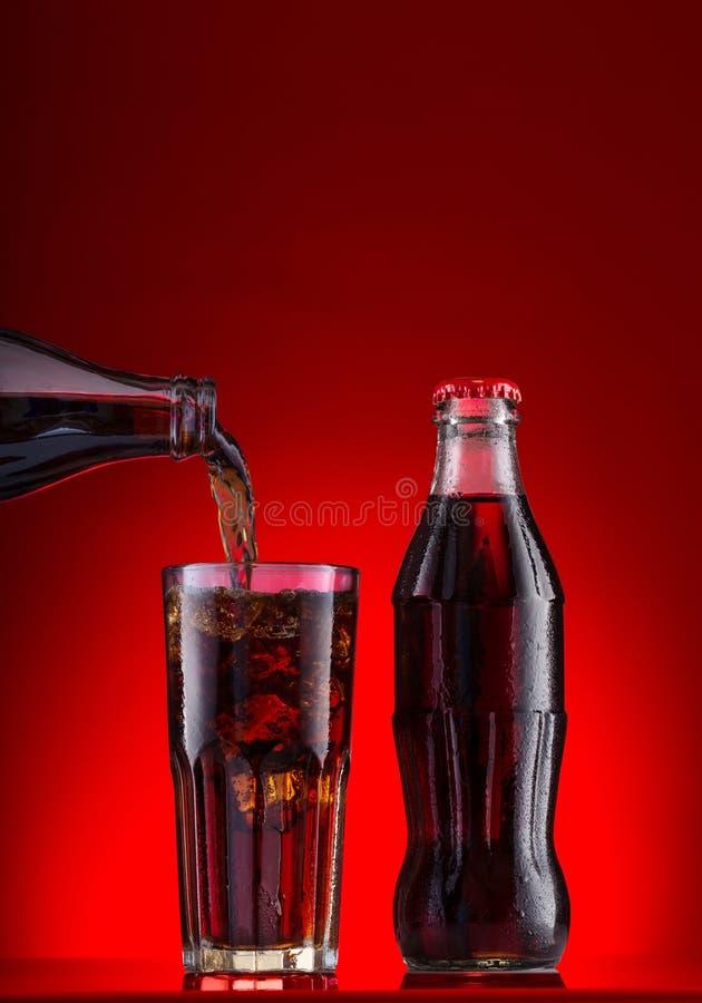 布朗碳酸饮料是与冰和瓶的倾吐的玻璃 库存图片