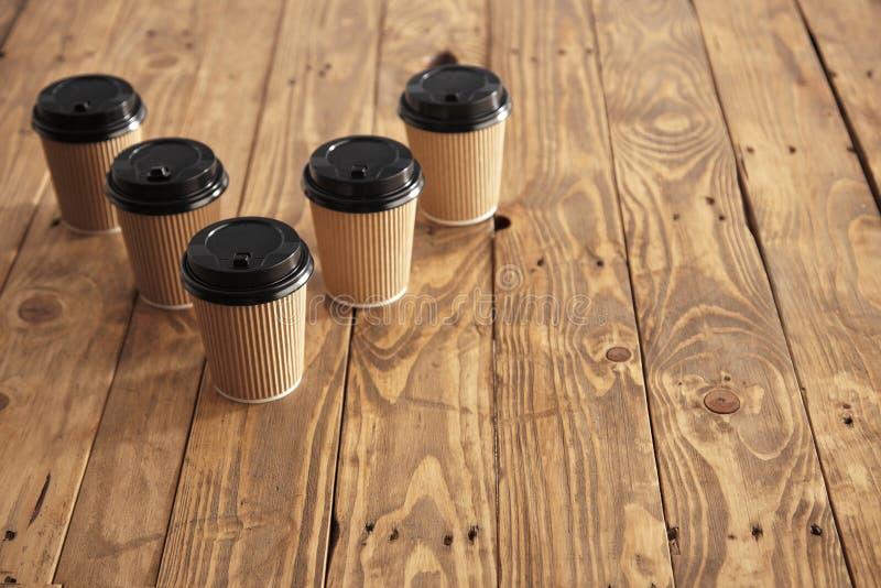 布朗纸板拿走有被设置的黑盖帽的纸杯 免版税库存图片