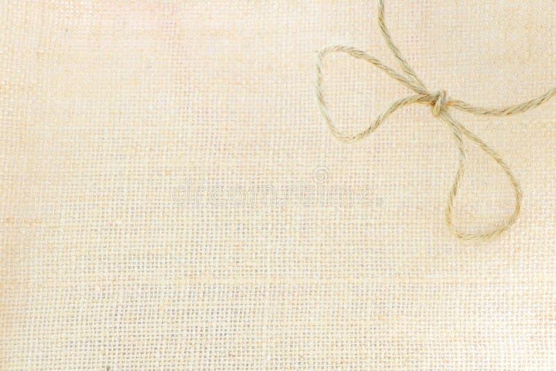 布朗绳索在大袋纹理背景的大袋弓 免版税图库摄影