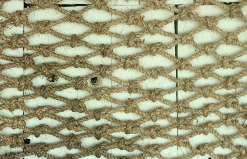 布朗自然绳索被栓对互相对障碍白色木板背景 自然绳索样式,纹理,背景 免版税图库摄影