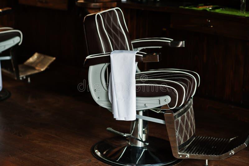 布朗葡萄酒皮椅在时髦的理发店 库存图片
