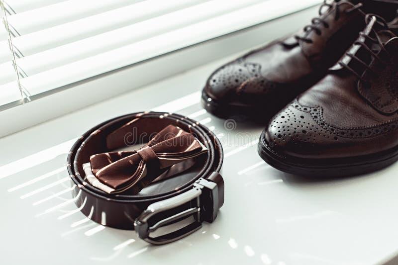 布朗蝶形领结、皮鞋和传送带 婚姻早晨的新郎 关闭时髦人士辅助部件 免版税库存照片